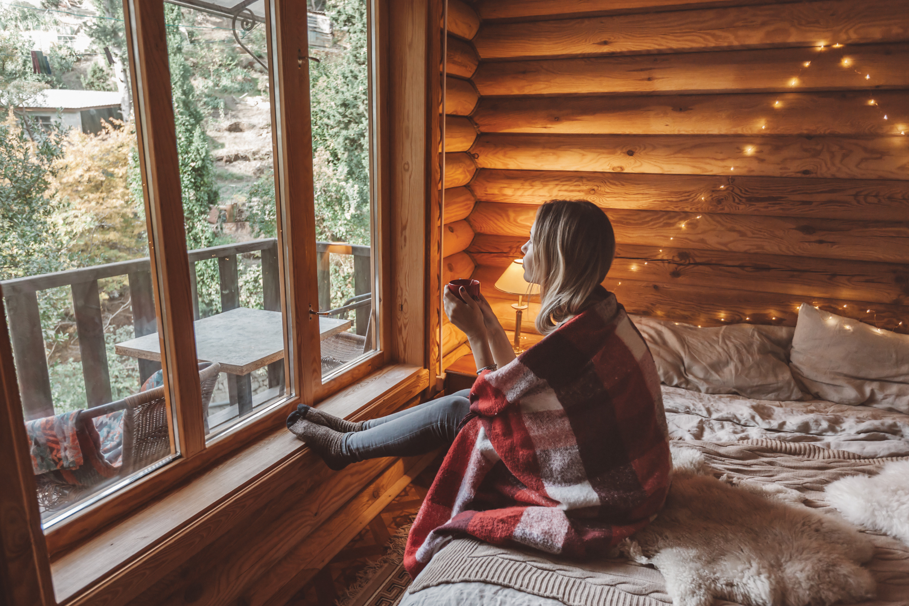 a woman drinking coffee, looking about a window from inside an ADU