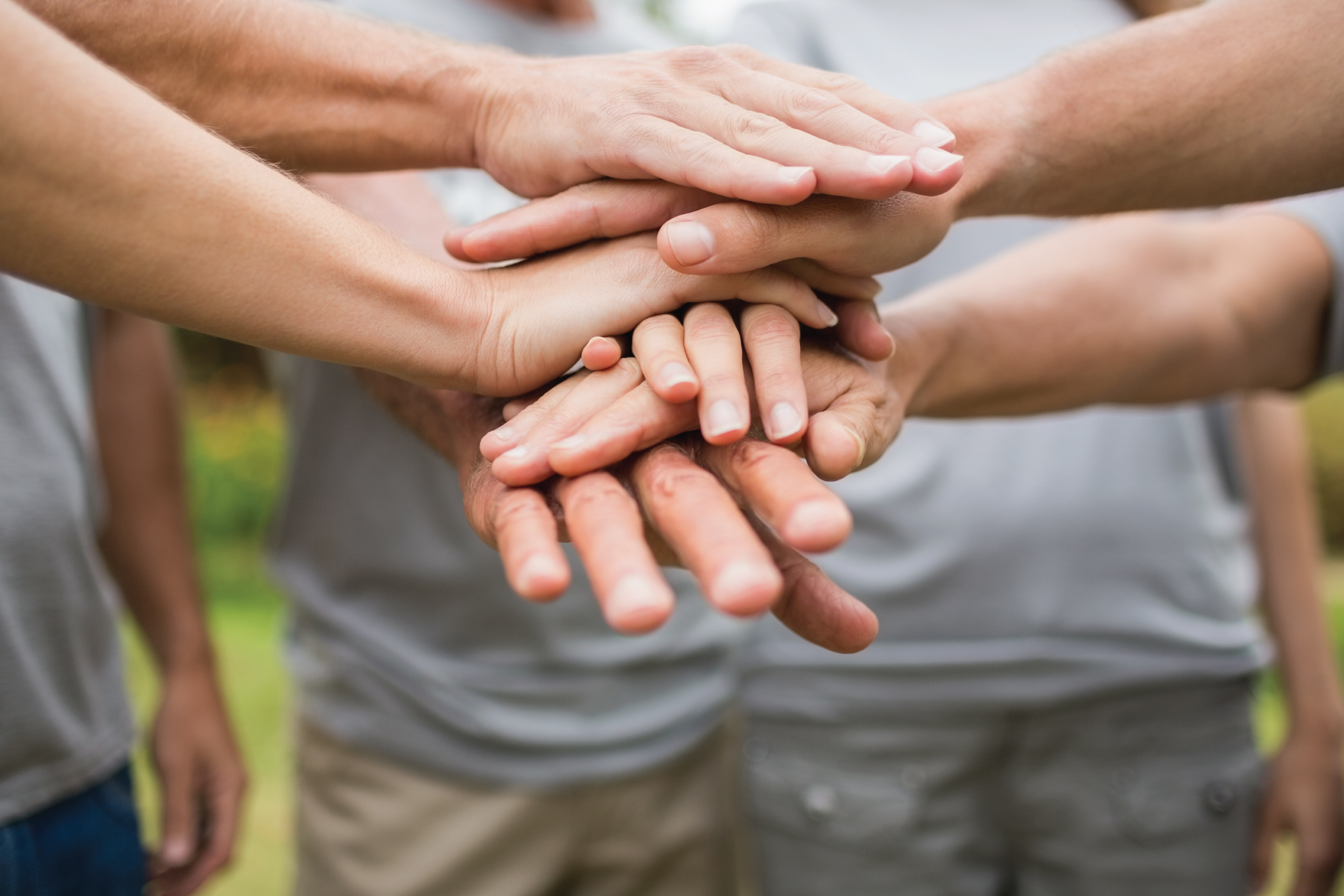 people putting their hands together in a huddle to show teamwork