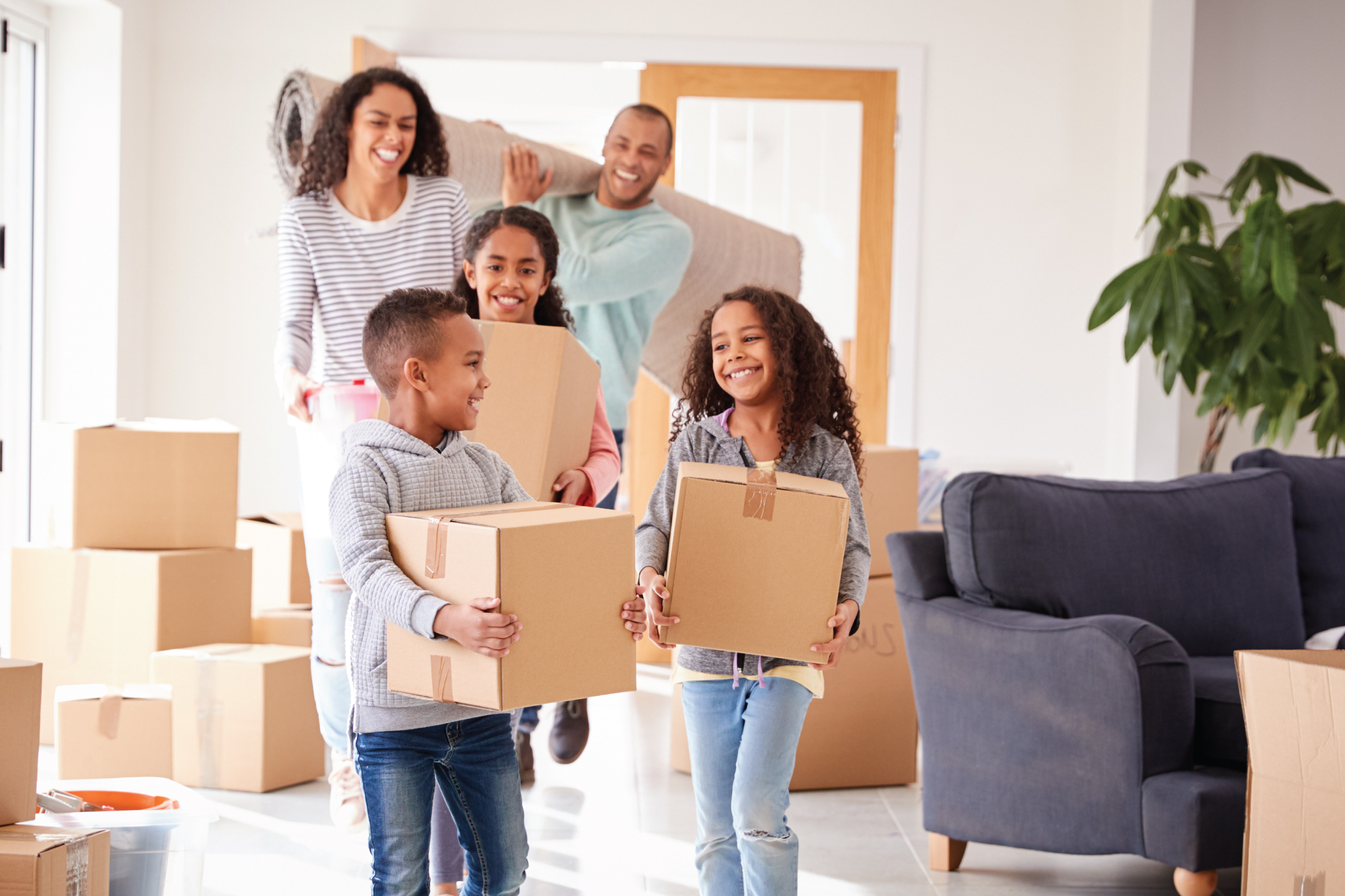 a family bringing moving boxes into their new home